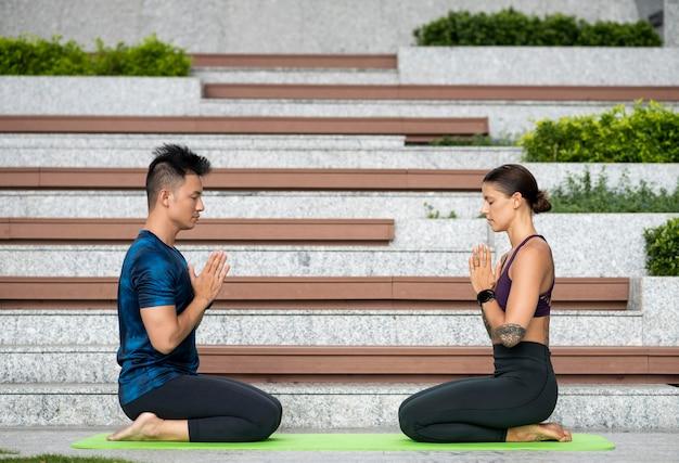 Uomo e donna che meditano mentre si fa yoga