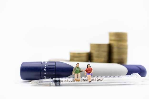 Man and woman miniature figure sitting on insulin syringe with lancet with stack of gold coins.
