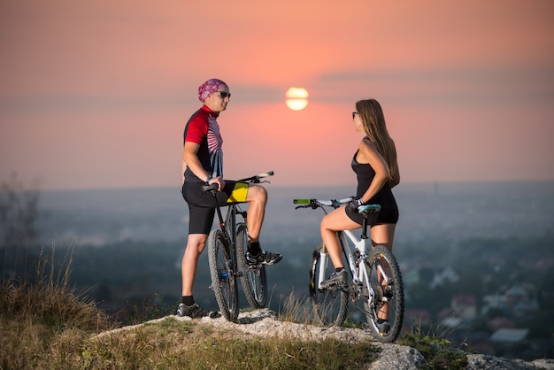 Man and woman on a mountain bikes standing on the cliff rocks turning back to the camera.