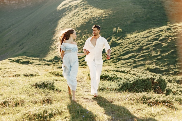 Man and woman in the mountains. young couple in love at sunset. woman in a blue dress.