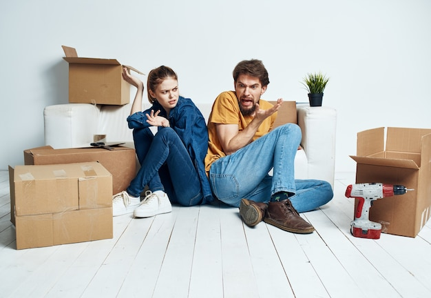 Man and woman moving apartment flower potted and boxes repair tools