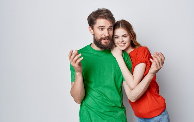 Man and woman in multicolored tshirts embrace studio