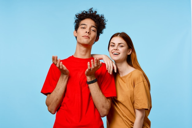 Man and woman in multicolored tshirts fashion posing blue background