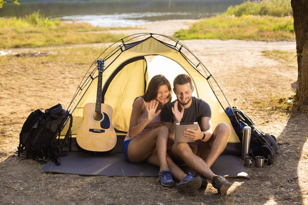A man and a woman near the tent with a tablet.