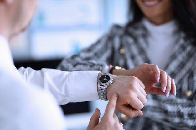 Man and woman in office check time on wristwatch