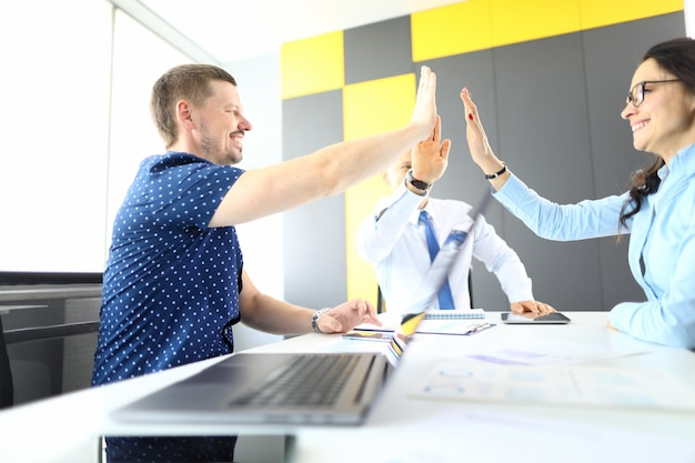 Man and woman in office holding hands in greeting