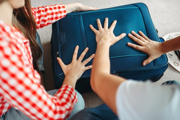 Man and woman packing their suitcases for vacation