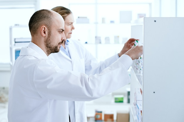 Man and a woman pharmacists discussing medicines