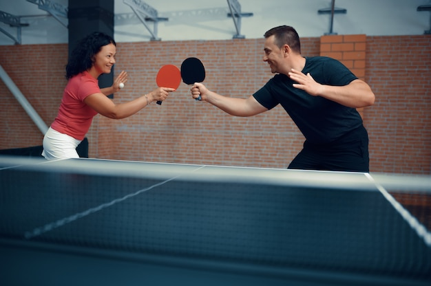Man and woman play table tennis