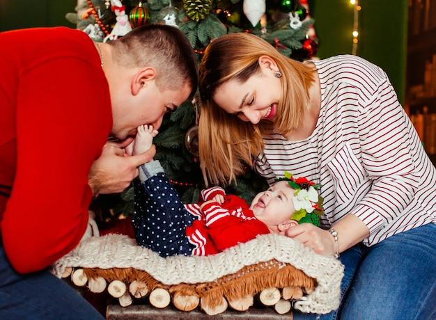 L'uomo e la donna giocano con la loro figlia mentre giace davanti a un albero di natale