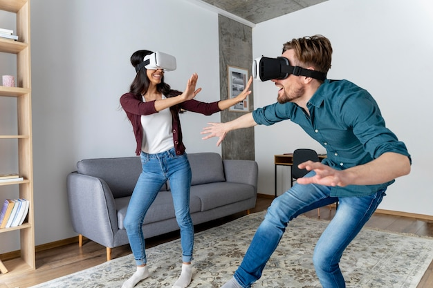 Man and woman play with virtual reality headset at home together