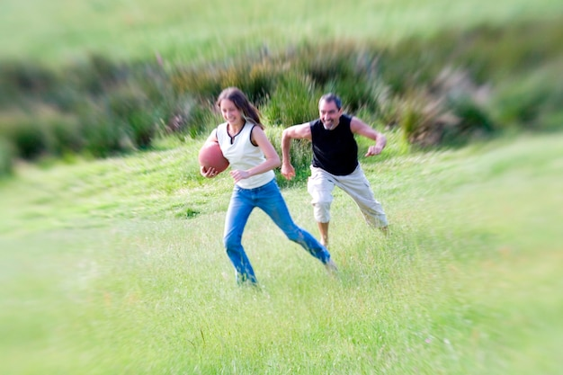 Man and woman playing ball in field