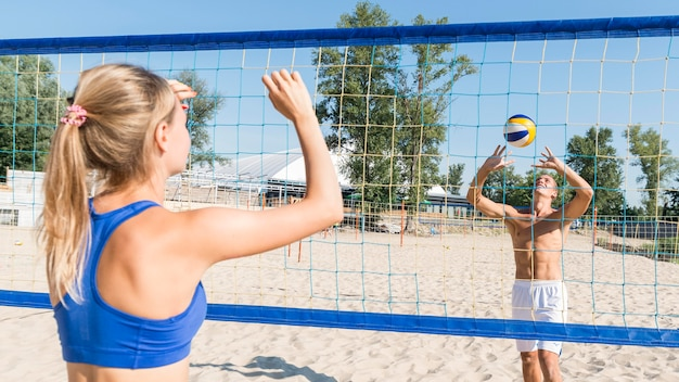 Man and woman playing beach volleyball together