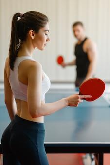 Man and woman playing ping pong indoors