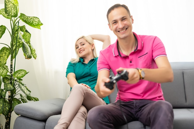 Man and woman playing video games with joystick at home.