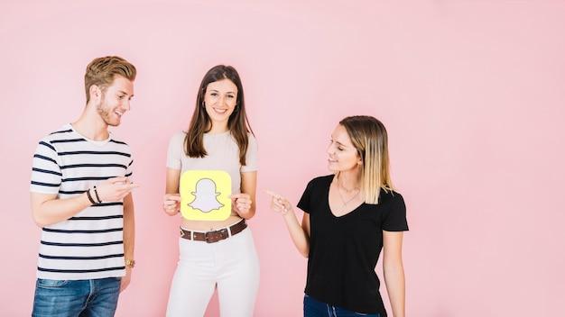 Uomo e donna che punta al loro amico felice che tiene icona snapchat