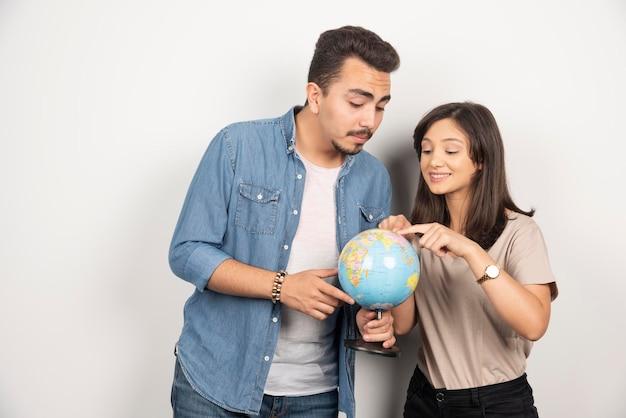 Uomo e donna in posa con il globo su bianco.