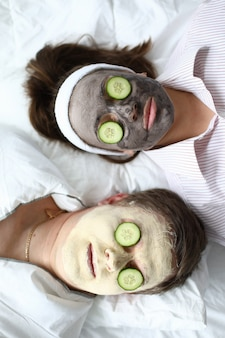 Man and woman put on face mask and cucumbers