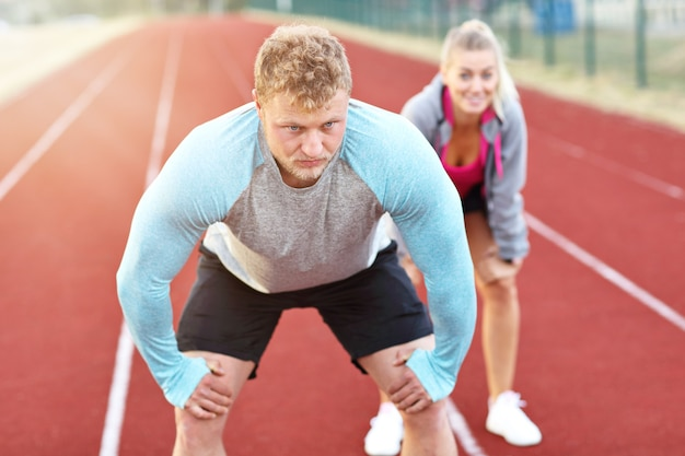 Man and woman racing on outdoor track