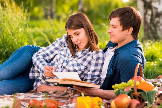 Man and woman reading book on picnic