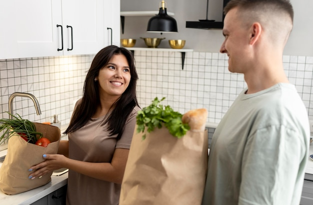 Man and woman receiving paper grocery bags after online shopping