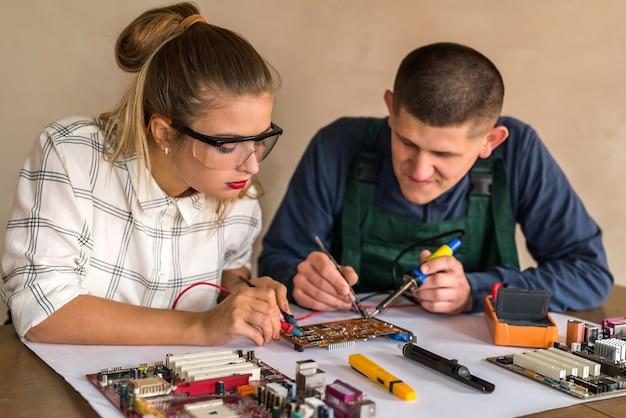 Man and woman repairing computer motherboard in workshop