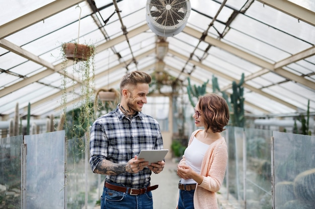 Man and woman researchers standing in greenhouse in botanical garden, using tablet.