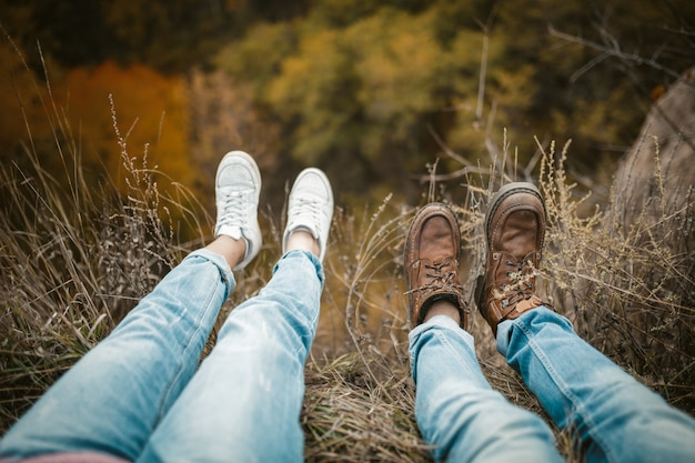 Man and woman rests on cliff edge with legs hanging down