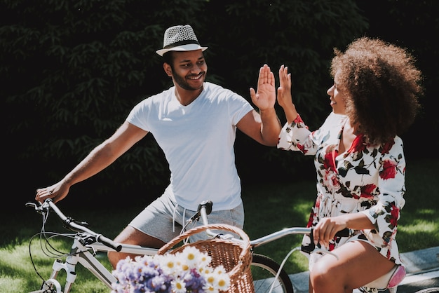 Man and a woman ride bicycles and give five to each other.