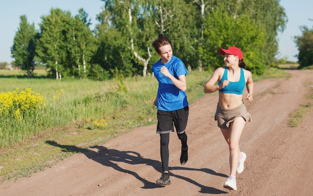 Man and woman run on a sunny summer evening along a country road against the background of a forest and smile at each other. side view