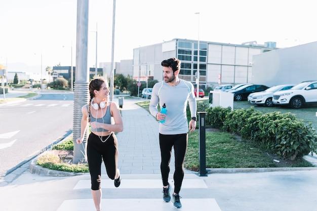 Man and woman running on crosswalk