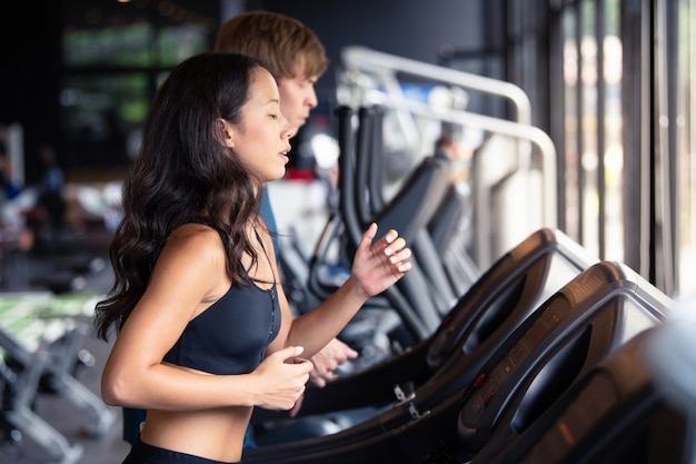 Man and woman running on machine work out for healthy at gym