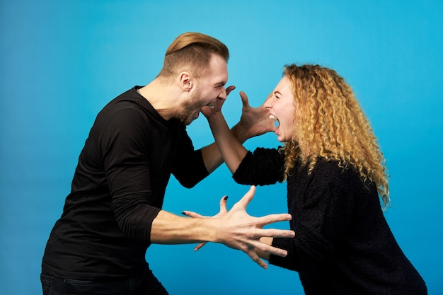 Man and woman screaming at each other, quarreling.