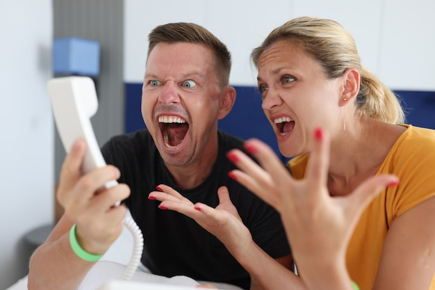 Man and woman shouting into telephone receiver in hotel room