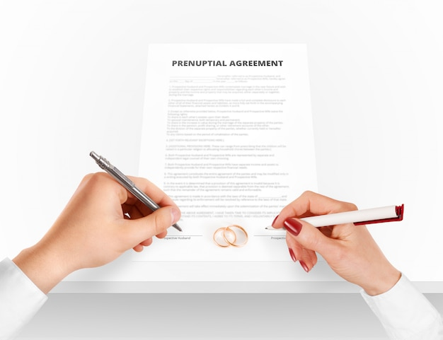 Man and woman sign prenuptial agreement near gold rings.