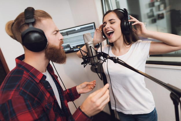 Man and a woman sing a song in a modern recording studio.