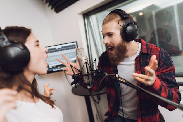 A man and a woman sing a song in a modern recording studio