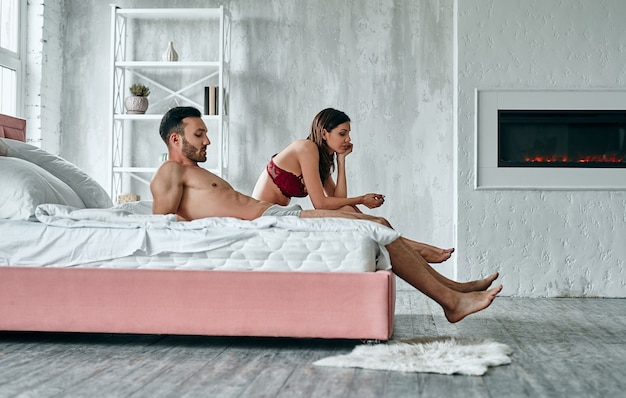 The man and woman sitting on the bed