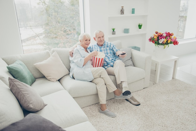 Man and woman sitting on a couch eating popcorn