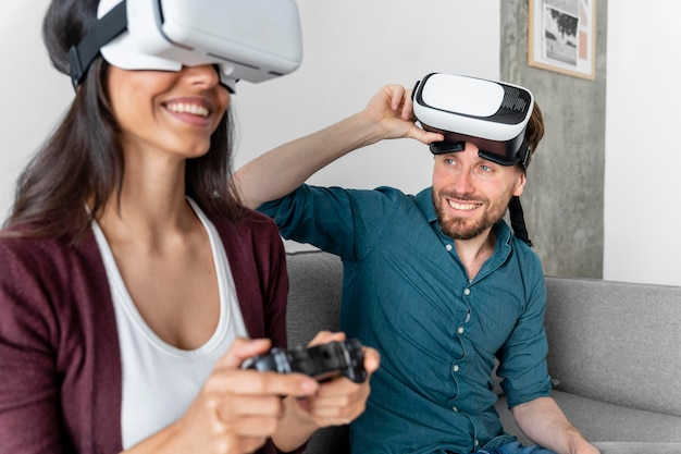 Uomo e donna che si siedono sul divano a casa e utilizzando le cuffie da realtà virtuale
