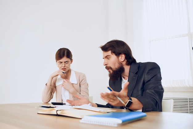 Man and woman sitting at the desk communication emotions work colleagues dissatisfaction