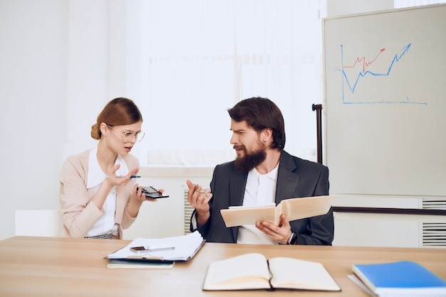 Man and woman sitting at a desk office work technology communication