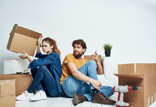 Man and woman sitting on the floor with their backs to each other renovation work