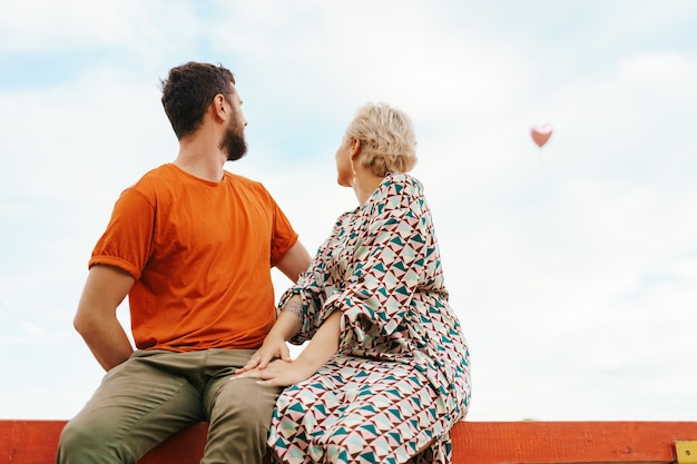 Uomo e donna che si siedono felici su una tavola di legno che guarda a un palloncino cuore rosa volante nel cielo