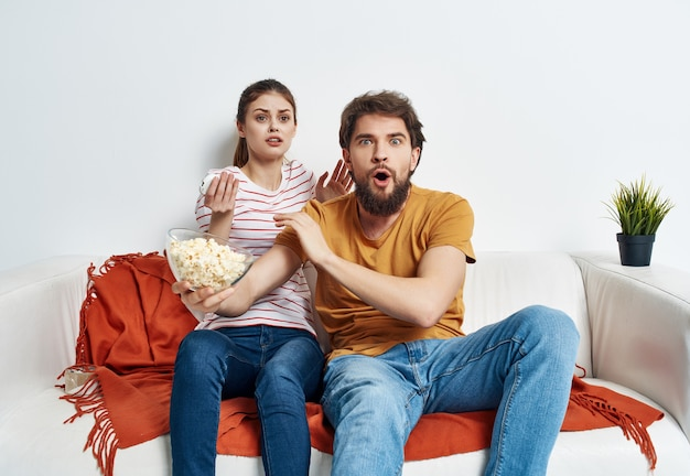 Man woman sitting at home on the couch viewing topic