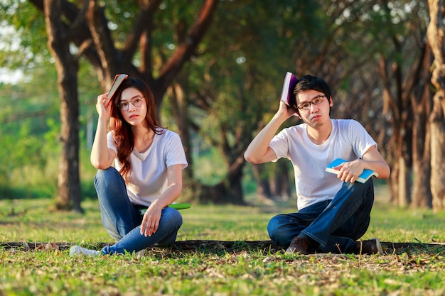 Man and woman sitting and reading a book in park