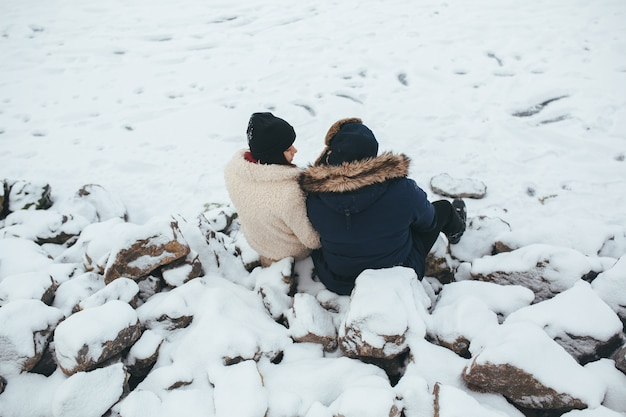 Man and woman sitting on the rocks covered with snow, on the shore of the lake