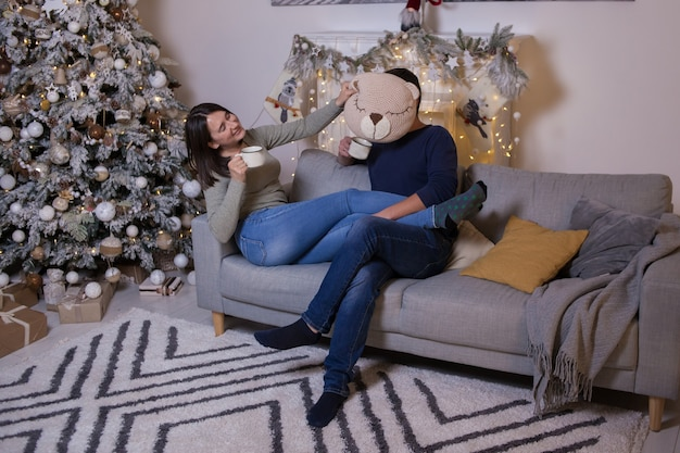 Man and woman sitting on the sofa and near christmas tree with presents and drink tea