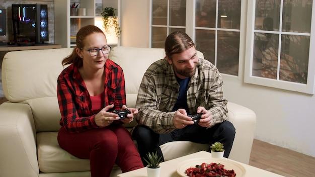 Man and woman sitting on sofa playing video games using wireless joysticks.