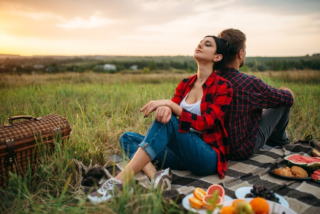 Man and woman sitting with their backs to each other on sunset, picnic in the field. romantic junket on sunset, couple on outdoor dinner,  happy relationships